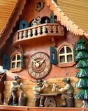 Cuckoo Clock from Black Forest. Gorgeous cuckoo clock with intricate carvings.  Clock shows almost two o'clock.  Men drinking ale, chopping wood, and dancing on Stock Photography