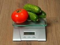 Cucmbers e tomate frescos nas escalas Fotos de Stock Royalty Free