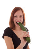The cucumber. A young woman eating a cucumber royalty free stock photos