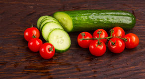 Cucumber amd tomatoes on wooden table Stock Photography