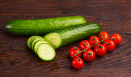 Cucumber amd tomatoes on wooden table Royalty Free Stock Photography