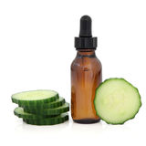 Cucumber Aromatherapy. Cucumber slices with aromatherapy essential oil glass bottle over white background Royalty Free Stock Images