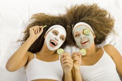 Cucumber and beauty. Young women with puryfing mask. Ther're lying on towels Stock Image