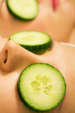 Cucumber beauty girls in spa. Girls in a beauty treatment in a spa setting with cucumber slices royalty free stock image
