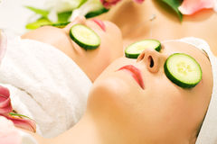 Cucumber beauty girls in spa. Girls in a beauty treatment in a spa setting with cucumber slices Royalty Free Stock Photo