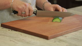 Cucumber being sliced on a cutting board stock video