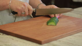 Cucumber being sliced on a cutting board stock video footage