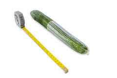 Cucumber with condom and measuring tape on white Royalty Free Stock Image