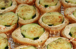 Cucumber cracker snacks. Close up of appetising cucumber slices on cracker biscuits, sprinkled with seafood spread Stock Images