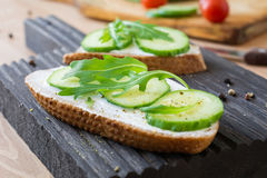 Cucumber, cream cheese and arugula toast. Light snack or breakfast. Healthy breakfast or snack: Cucumber, cream cheese and arugula toast on wooden cutting board Stock Photo