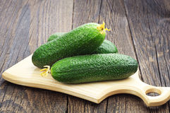 Cucumber on cutting board. Three fresh cucumber on cutting board Stock Photo