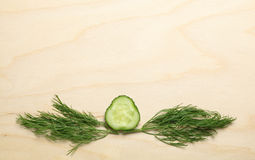 Cucumber and dill twigs on chopping board Stock Photos