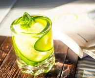 Cucumber drink on book. Cucumber drink in tumbler garnished with mint on text books Stock Photos