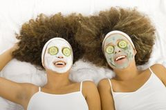 Cucumber-eyes. Happy twins with anti-aging face masks. Cucumber slices covering theirs eyes. Ther're lying on towels royalty free stock photo