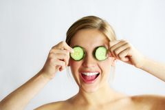 Cucumber face mask. A young beautiful woman in wellness with a cucumber against her face stock image