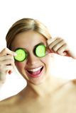 Cucumber face mask. A young beautiful woman in wellness with a cucumber against her face Stock Images