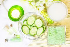 Cucumber home spa and hair care concept. Sliced cucumber, bottles of oil, sea salt, bathroom towel. Straw light background stock photo