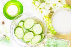 Cucumber home spa and hair care concept. Sliced cucumber, bottles of oil, sea salt, bathroom towel. Straw light background royalty free stock photos