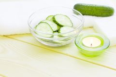 Cucumber home spa and hair care concept. Sliced cucumber, bottles of oil, sea salt, bathroom towel. White board background stock photo