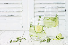 Cucumber infused hydrating water with thyme and lime. Homemade flavored lemonade on rustic old wooden table. Cucumber infused hydrating water with thyme and Stock Photography