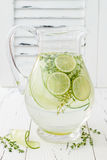 Cucumber infused hydrating water with thyme and lime. Homemade flavored lemonade on rustic old wooden table. Cucumber infused hydrating water with thyme and Stock Photo