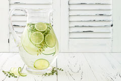 Cucumber infused hydrating water with thyme and lime. Homemade flavored lemonade on rustic old wooden table. Cucumber infused hydrating water with thyme and Stock Photos