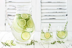 Cucumber infused hydrating water with thyme and lime. Homemade flavored lemonade on rustic old wooden table. Cucumber infused hydrating water with thyme and Royalty Free Stock Photos