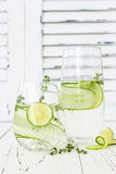 Cucumber infused hydrating water with thyme and lime. Homemade flavored lemonade on rustic old wooden table. Cucumber infused hydrating water with thyme and Royalty Free Stock Image