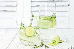 Cucumber infused hydrating water with thyme and lime. Homemade flavored lemonade on rustic old wooden table. Cucumber infused hydrating water with thyme and Royalty Free Stock Photo