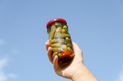 Cucumber jar in female hand on blue sky background Royalty Free Stock Images