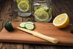 Cucumber and lemon slices on a cutting board and a jar on the background Stock Images