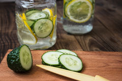 Cucumber and lemon slices on a cutting board and a jar on the background Royalty Free Stock Photography