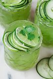 Cucumber and lime alcoholic cocktails on white marble surface Stock Images