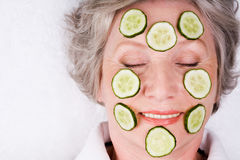Cucumber mask. Face of mature woman with cucumber slices on it stock photography