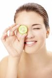 Cucumber mask. Portrait of the playful girl covering an eye by a slice of a cucumber, isolated royalty free stock photos
