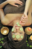 Cucumber mask on face. Woman eat cucumbers from her face Royalty Free Stock Photos