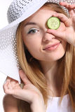 Cucumber mask. Woman in a hat with cucumber on eyes royalty free stock image