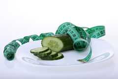Cucumber and measuring tape Stock Images