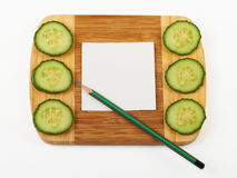 Cucumber and notepad on wooden board. Stock Images