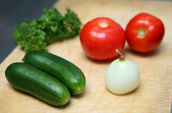 Cucumber, onion and tomato. On a kitchen table Stock Photos
