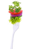 Cucumber, onion, tomato and parsley on a fork. Lettuce, cucumber, onion, tomato and parsley on a fork isolated on white background Royalty Free Stock Image