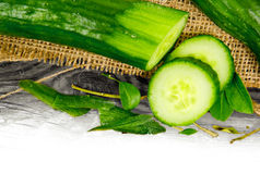 Cucumber. Photo of cucumber, slices and leaves on burlap and wooden board with white space stock image