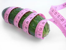 Cucumber with pink tape measure over white background Stock Images