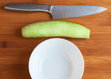 Cucumber, plate and knife on a cutting board. Stock Photography