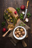 Cucumber, radishes, lettuce, mustard, potatoes on a cutting board top view. Vertical Stock Photography