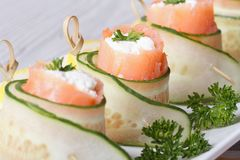 Cucumber rolls with salmon, cream cheese macro horizontal Royalty Free Stock Images