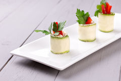 Cucumber rolls on white plate. Cucumber spring rolls with soft cheese, parsley and red bell pepper on white plate royalty free stock photo