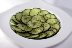 Cucumber salad. Closeup of a cucumber salad in a white dish or platter on a white background Royalty Free Stock Photo