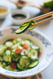 Cucumber salad in Chinese chopsticks Stock Photo