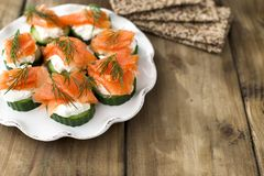 Cucumber and salmon, small snacks on a plate. Copy space royalty free stock photography